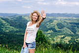 Girl waves her hand in the mountains