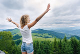 Woman standing on cliff's edge with raised hands