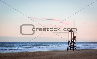 Beach sunrise with vintage lifeguard wood tower