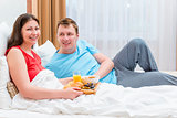 a married couple together breakfast in bed
