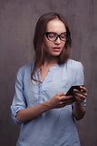 portrait of smiling woman with glasses and cellphone near grey background wall