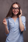 portrait of smiling woman with glasses speaking by cellphone near grey background wall