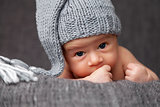 Beautiful newborn wearing a cute grey hat