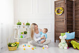 Delighted mother and her child enjoying the Easter egg hunt at home