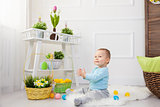 Easter egg hunt. Adorable child playing with Easter eggs at home