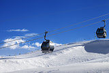 Gondola lifts on ski resort at sun wind day