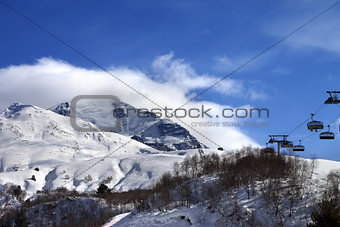 Ski-lift, off-piste slope and mountain in clouds