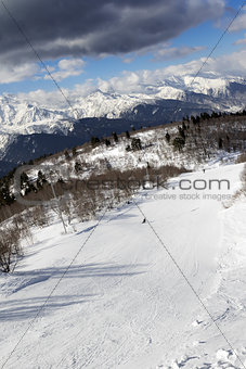 Skiers on ski slope at sun winter day