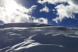 Off-piste slope during blizzard and sunlight blue sky with cloud