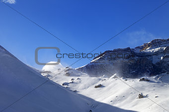 Off-piste slope during blizzard and sunlight blue sky