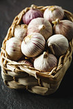 Garlic gloves in a basket on dark grey background