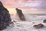 Wave surges through rocky coastline at sunrise