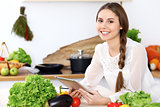 Young  happy woman is making online shopping by tablet computer while smiling. Housewife looking for a new recipe for  cooking in a kitchen