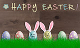 colorful pastel easter eggs with bunny ears on wooden background, promotional sign with text happy easter