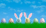 colorful bright pastel easter eggs with bunny ears in grass with blue sky background, copy space