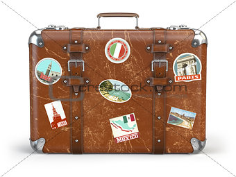 Old suitcase baggage with travel stickers isolated on white back