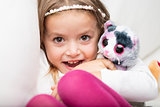 Cute laughing little girl with her fluffy toy