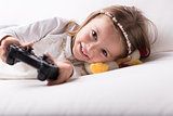 Smiling pretty little girl playing video games