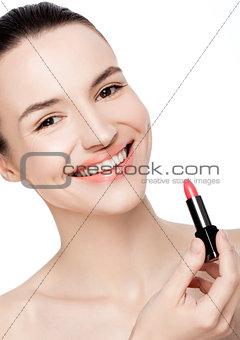 Beautiful model girl holding lipstick tube makeup