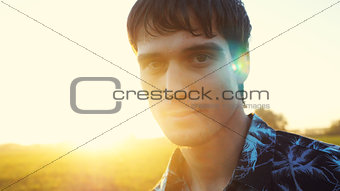 Portrait of man looking at the sun during beautiful sunset with lense flare effects.