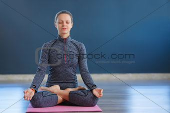 Beautiful young woman sitting in Lotos pose. woman practicing meditation in yoga hall after hard day.
