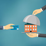 Hands holding credit card and cloche with house.