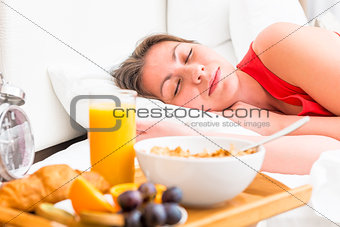 breakfast on a tray beside the bed sleeping girl
