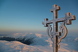 Frosted cross against beautiful sunrise scene in mountains
