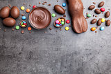 Chocolate Easter bunny, eggs and sweets on rustic background