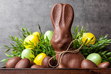 Traditional Easter chocolate bunny and eggs inside a wooden crate