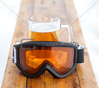 Ski goggles and glass mug with fresh cold beer