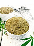 Flour hemp and grain in bowls with leaf on board