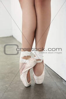 Close up of ballerina's feet in pointe shoes over a grey background