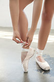 Ballerina laces the pointes on a grey background