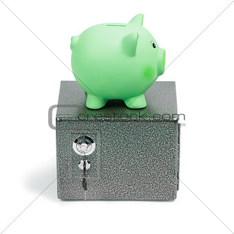 Green ceramic piggy bank standing on a safe