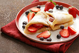 Thin pancakes crepes with berries for dessert