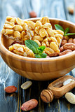 Honey bars with peanuts and peanut fruits in a wooden bowl.