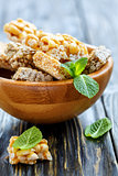 Wooden bowl with honey bars with peanuts, sesame seeds and sunfl