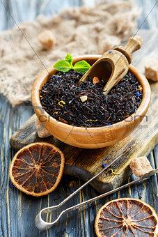 Black tea in bowl, cane sugar and tongs for sugar.