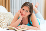 brunette girl with a book lying on the bed