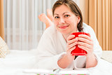 resting girl in bathrobe drinking tea in bed