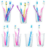 collection of tooth brushes in clear glasses