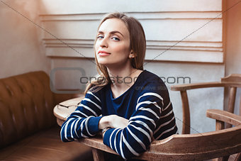Portrait of smiling female hipster waiting for meeting with best friend while during coffee break in cafe. Grey background with copy space area for advertising content