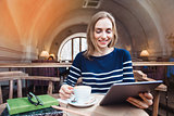 A smile young woman in the cafe with a cup of coffee looking at the digital tablet. Young girl with a cup of coffee and reading viewing internet in tablet while relaxing in a cafe.