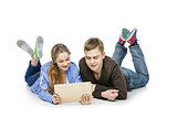 Teen boy and girl sitting with tablets
