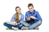Teen age boy and girl with tablet and notebook