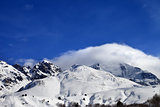 Mountains in clouds and off-piste slope in winter