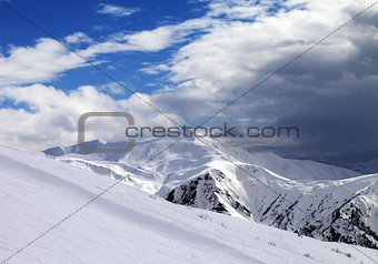 Ski slope in evening and storm clouds