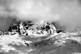 Black and white view on Mount Ushba in fog at sun winter day