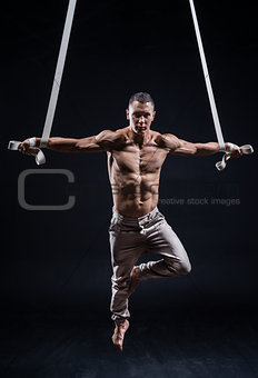 circus artist on the aerial straps man